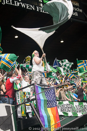 Sunday White waving her support of the Timbers above her rainbow flag